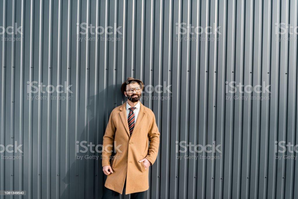 handsome businessman in coat standing against sunshine near textured...