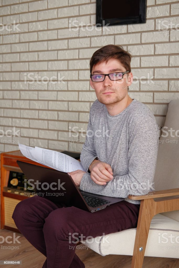 Gut aussehend Geschäftsmann in Gläsern arbeiten auf einem Laptop mit Arbeitspapieren und direkt in die Kamera schaut. Elegante Mann im Anzug hält den Vertrag. – Foto