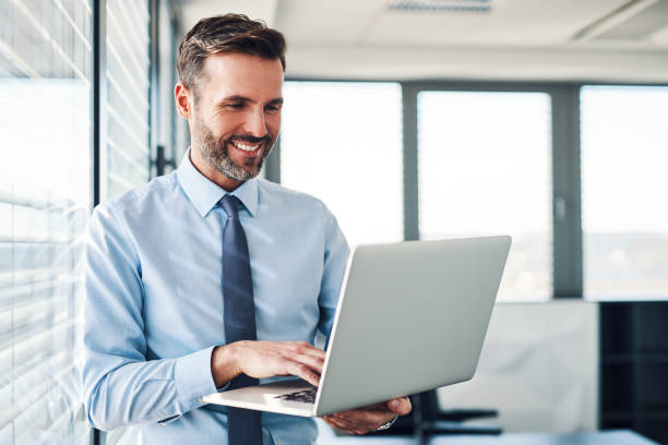 Handsome businessman in modern office looking on laptop stock photo