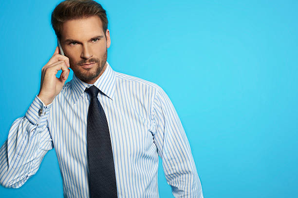 Handsome businessman in shirt and tie speaking on the phone stock photo