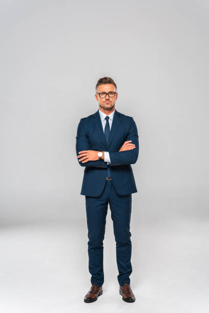 スーツと眼鏡立っている組んだ腕と白で隔離カメラ目線でハンサムな実業家 - 腕組み スーツ ストックフォトと画像