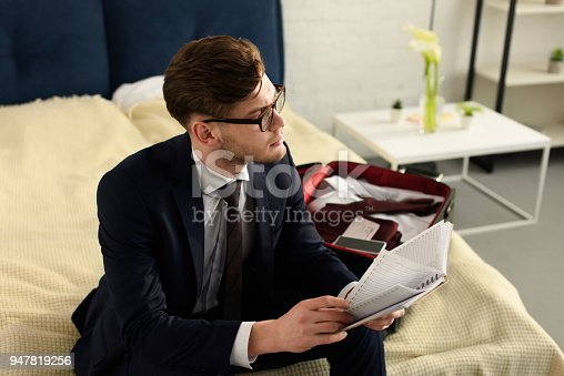 istock handsome businessman in suit reading diary while packing travel bag 947819256