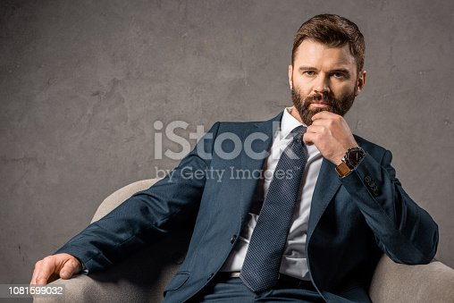 istock handsome businessman in suit sitting in armchair 1081599032