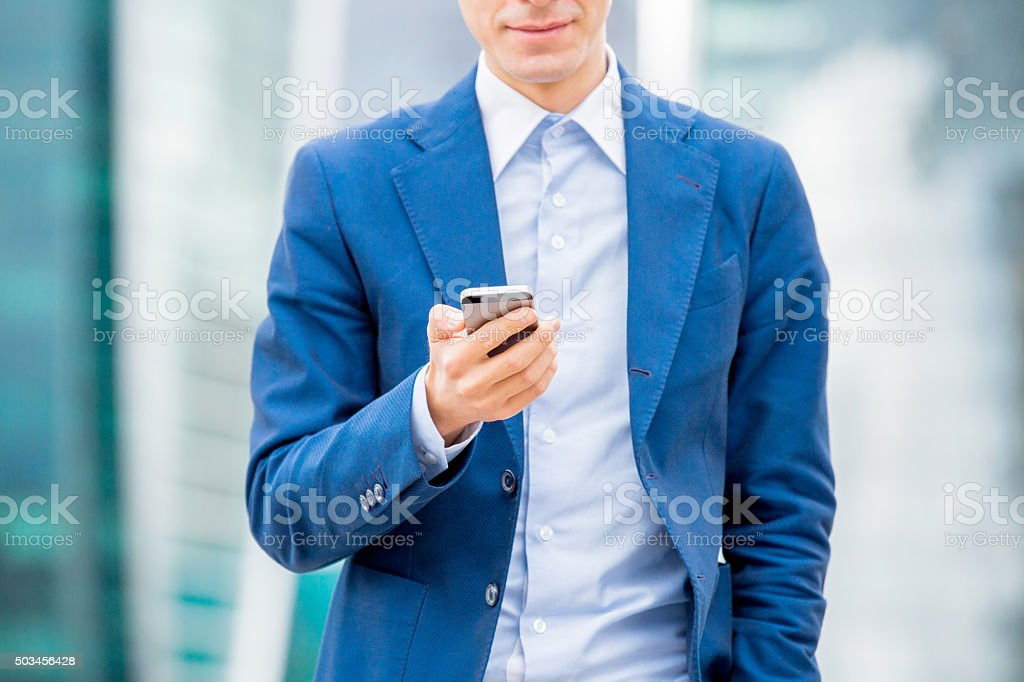 Handsome businessman in suit with smart phone in hand​​​ foto