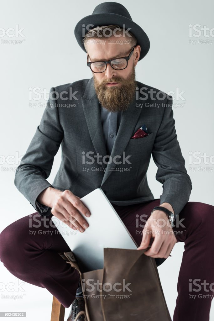 Handsome businessman in vintage style clothes with laptop and backpack isolated on light background - Zbiór zdjęć royalty-free (Biznes)