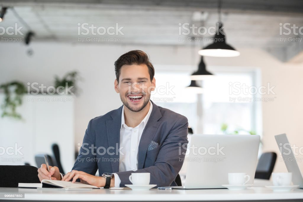 Handsome businessman laughing at his desk Portrait of handsome young businessman working in modern office and laughing 25-29 Years Stock Photo