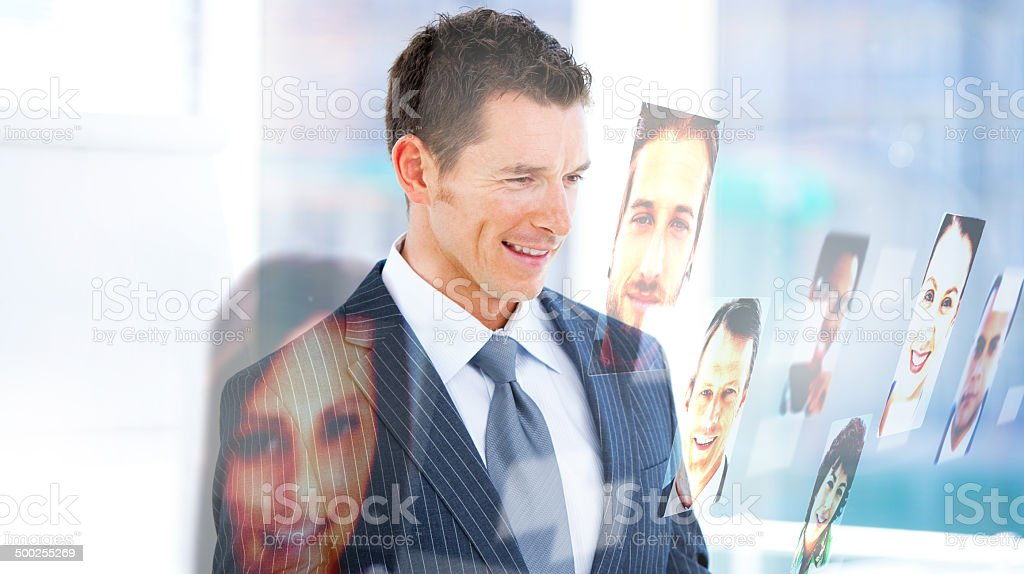 Handsome businessman looking at profile pictures royalty-free stock photo
