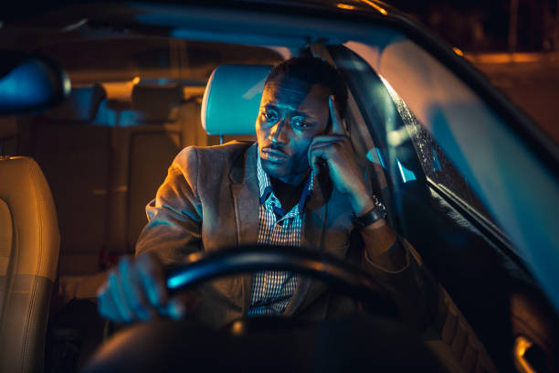 Handsome businessman on a business trip, driving at night. African ethnicity stock photo
