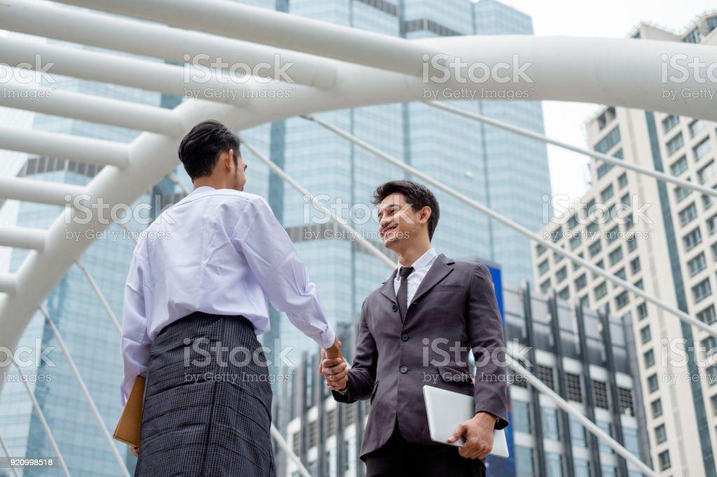 Handsome businessman partnership with handshake agreement of asean economics community in city stock photo