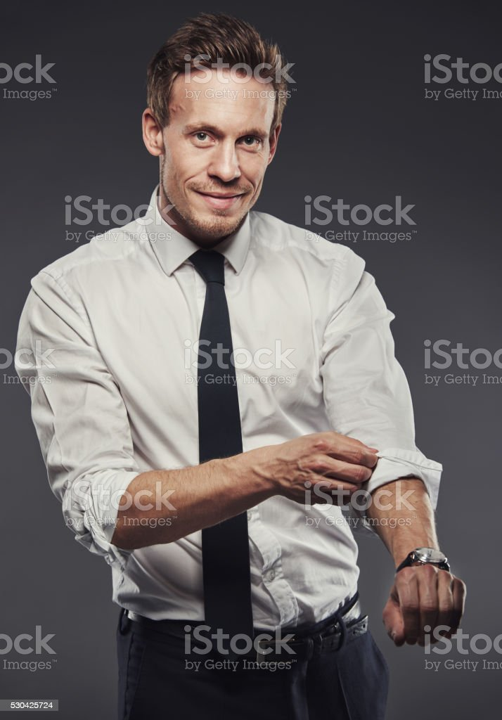 Handsome businessman rolling up his sleeves stock photo
