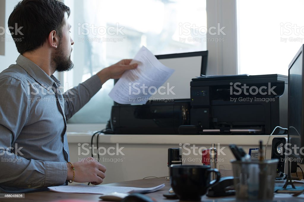 Handsome businessman scanning and printing document in office stock photo