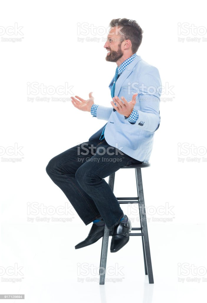 Handsome businessman seated on stool stock photo