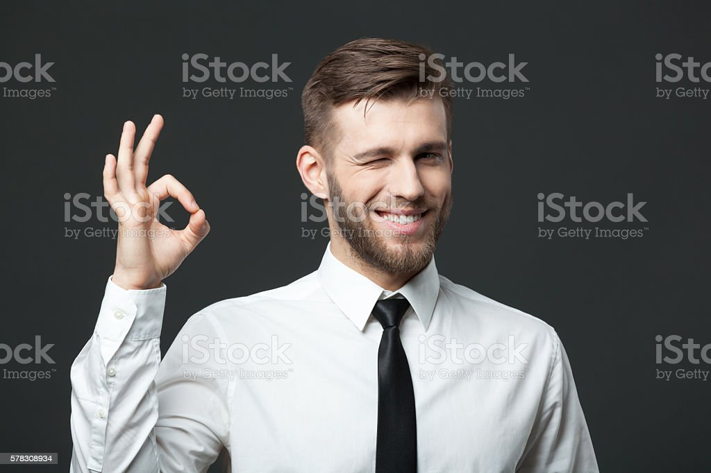 Handsome businessman showing okay sign on gray background. stock photo