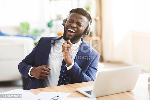 1003539592 istock photo Handsome businessman singing and listening to music with headphones 1179955029