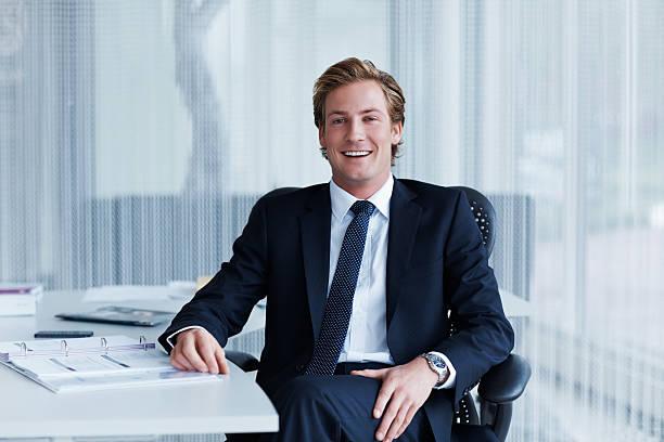 handsome businessman sitting at desk - netherlands map stockfoto's en -beelden