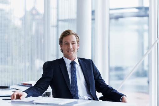 Portrait of handsome businessman sitting at desk in office