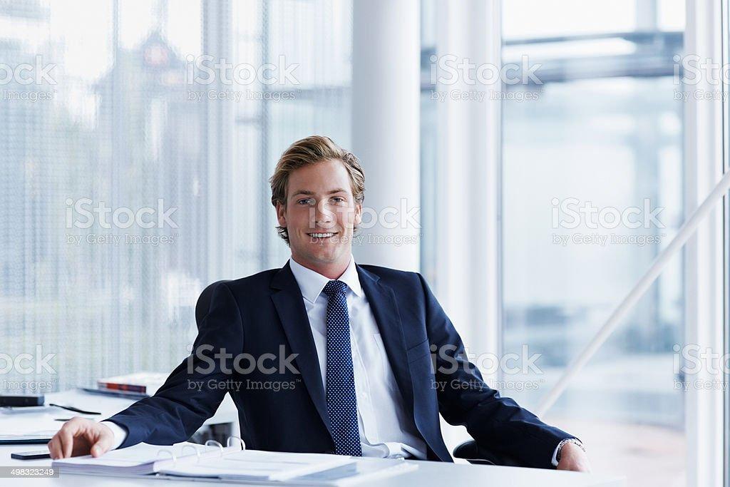 Handsome businessman sitting at desk - foto stock