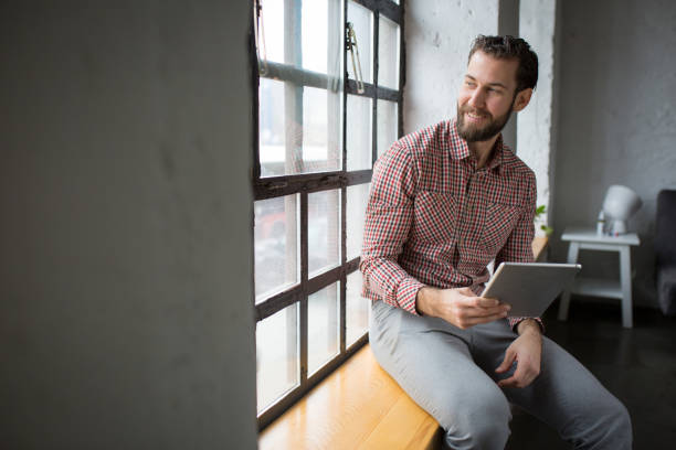 Handsome businessman sitting by the window and looking away stock photo