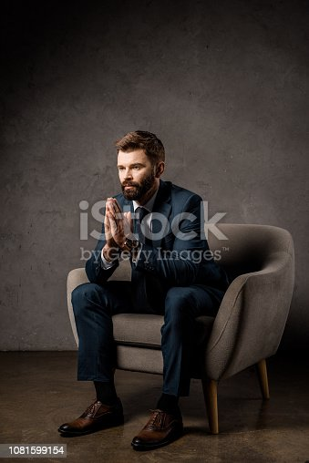 1081599130 istock photo handsome businessman sitting in armchair with praying hands 1081599154