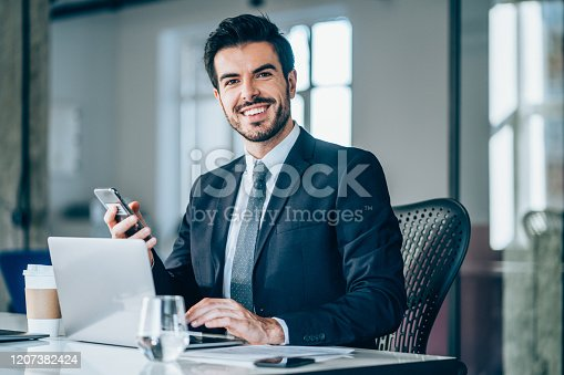 Shot of a young businessman sitting on desk in modern office and looking at camera. Portrait of a handsome businessman working on laptop and using smart phone in the office.