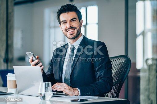 istock Handsome businessman sitting in modern office. 1207382424
