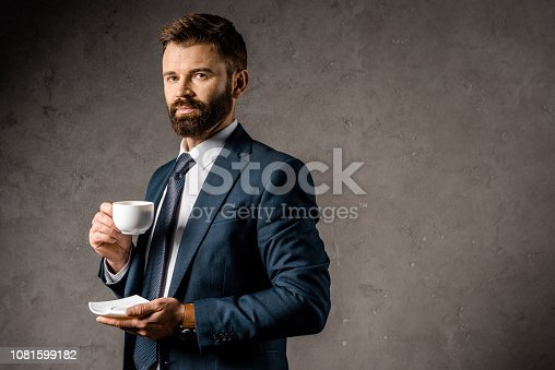 1081599130 istock photo handsome businessman standing with cup of coffee 1081599182