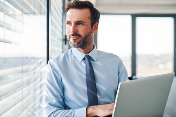 Hübsche Geschäftsleute stehen mit Laptop, Blick durch das Fenster in modernen Büro – Foto
