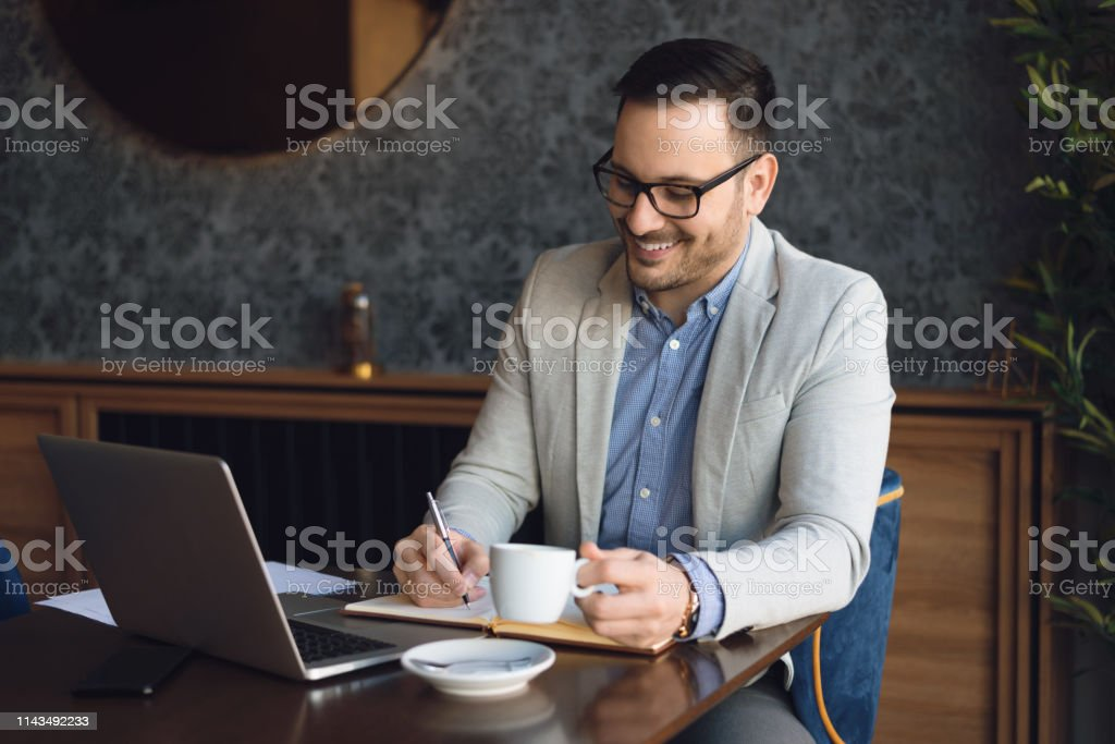 Young businessman writing something in a notebook and drinking coffee...