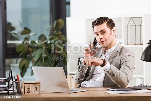 handsome businessman talking by phone at workplace in office and looking at camera
