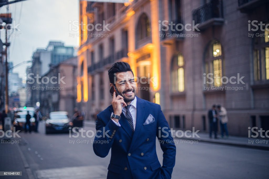 Handsome businessman talking on mobile phone outdoors stock photo