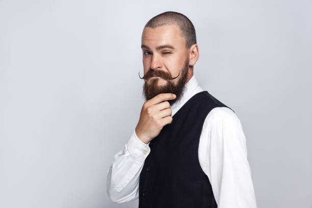 Handsome businessman thinking. thoughtful, Handsome businessman with beard and handlebar mustache looking at camera and thinking. studio shot, on gray background. mustache stock pictures, royalty-free photos & images