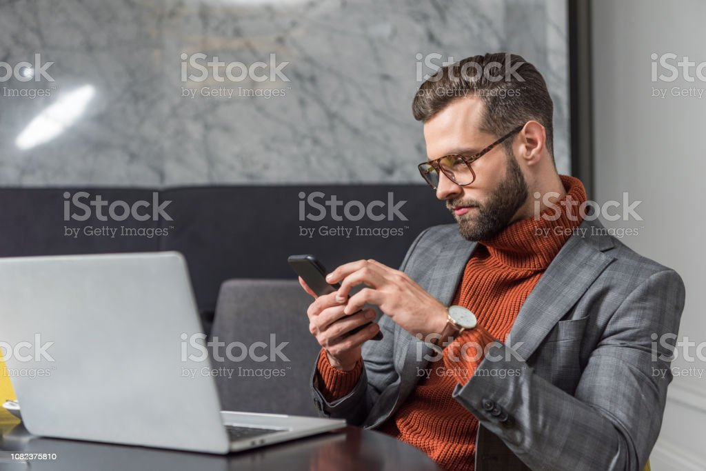 handsome businessman using smartphone and sitting at table with laptop in restaurant - Royalty-free Adult Stock Photo