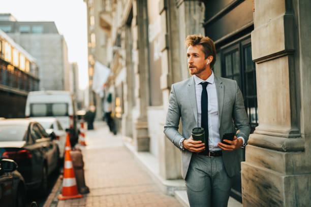 Handsome businessman walking stock photo