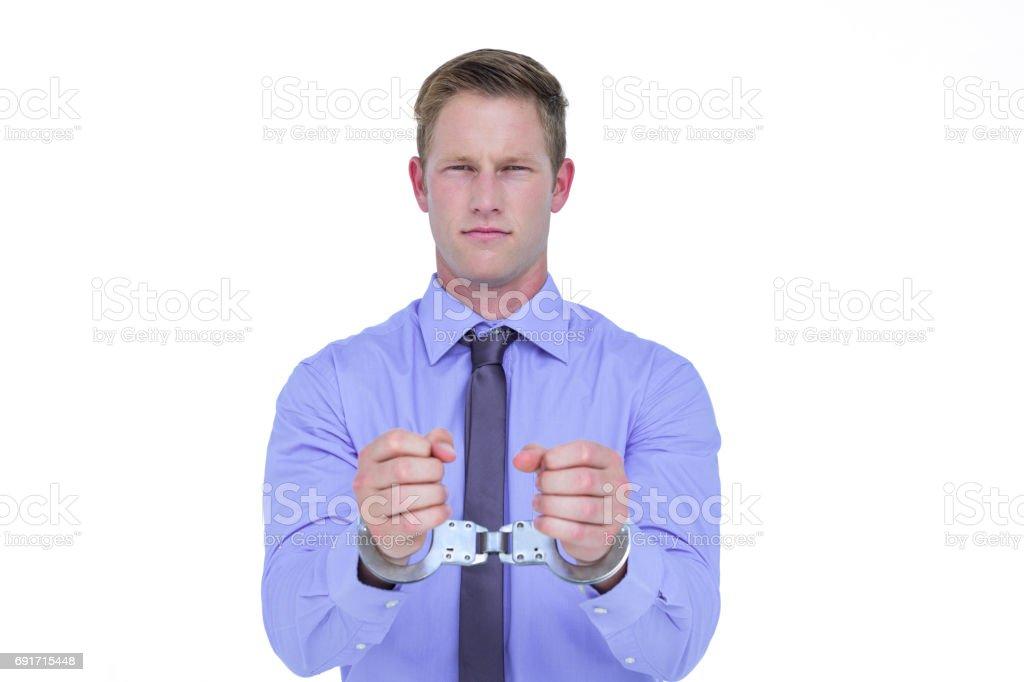 Handsome businessman wearing handcuffs stock photo