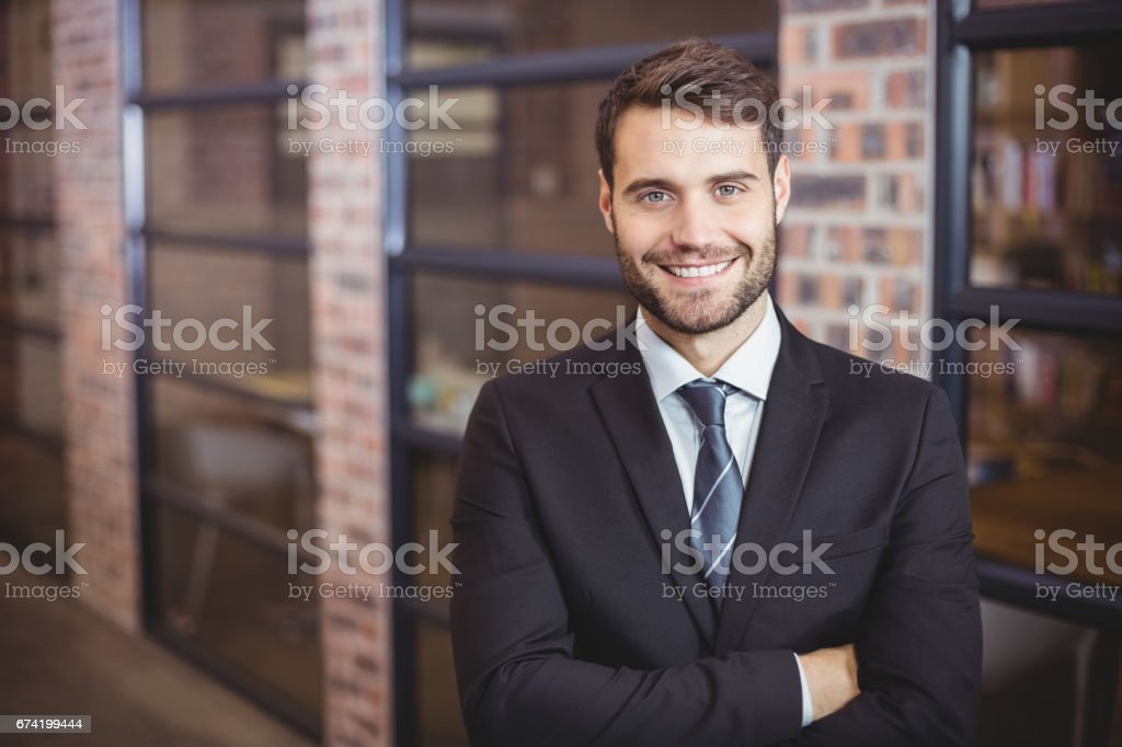 Handsome businessman with arms crossed standing in office stock photo
