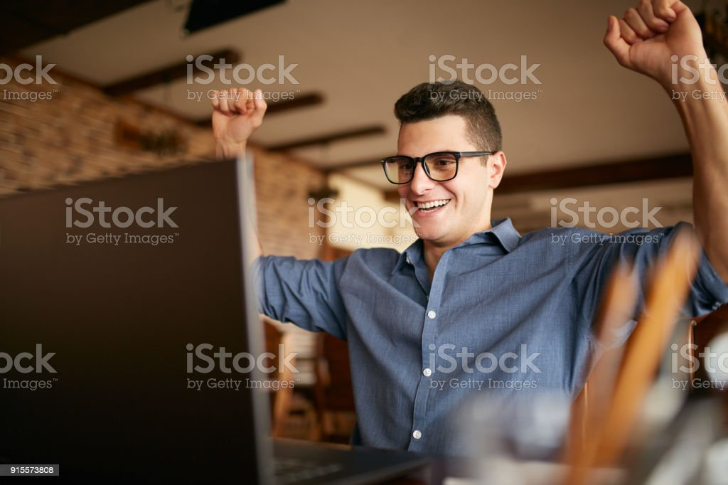 Handsome businessman with laptop having his arms with fists raised, celebrating success. Happy freelancer hipster in glasses finished work on project. Man won a lot of money in lottery prize stock photo