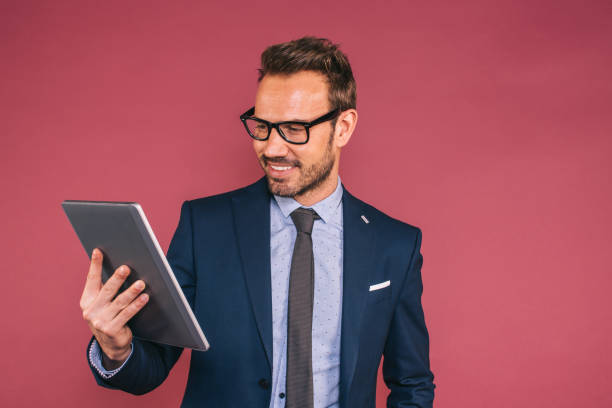 Handsome businessman working in a tablet stock photo