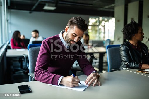 Close up  of young, handsome, businessman writing on paper in the office space, concentrated