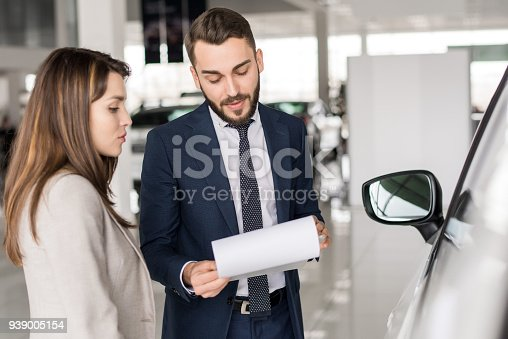 istock Handsome Car Salesman Talking to Client 939005154