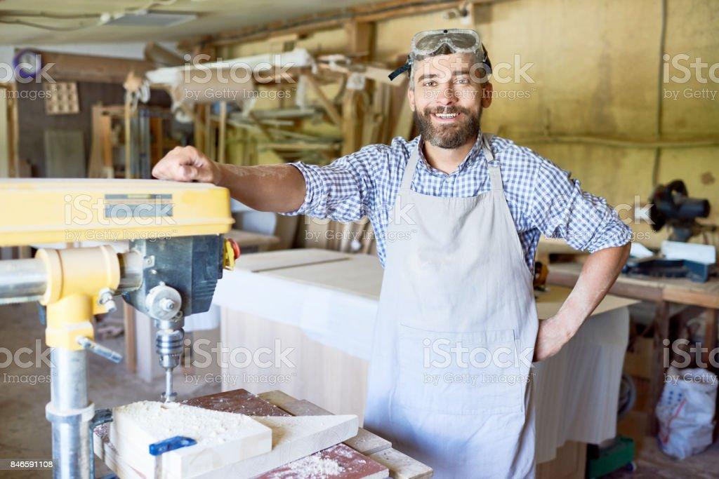 Handsome Carpenter at Drill Press Machine stock photo