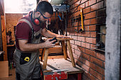 istock Handsome Carpenter Polishing a Footstool in his Workshop 1298607035