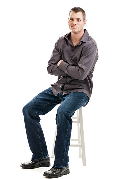 Handsome casual businessman portrait Full length portrait of a mid 30s casual business man with arms folded sitting on a stool isolated on a white background stool stock pictures, royalty-free photos & images