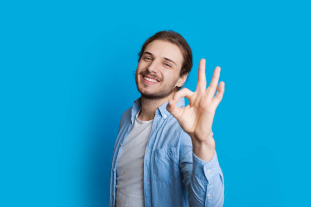 Handsome caucasian boy gesturing approbation sign while smiling and posing on a blue background Handsome caucasian boy gesturing approbation sign while smiling and posing on a blue background approbation stock pictures, royalty-free photos & images