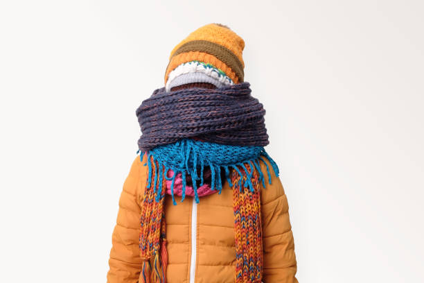 Handsome caucasian funny man hiding face in several hats and scarfs. stock photo