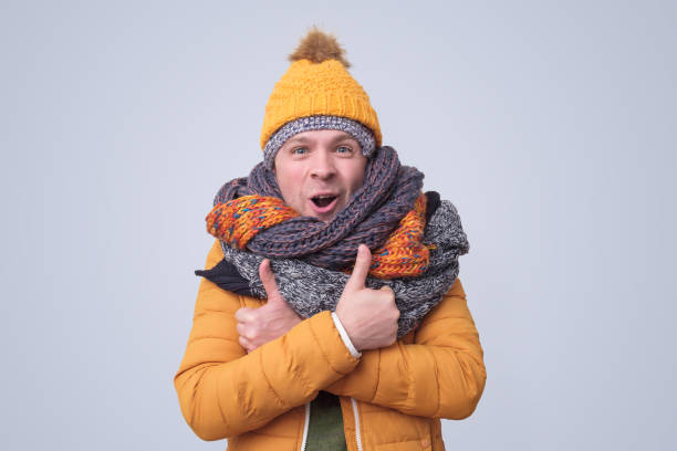 Handsome caucasian funny man in several hats and scarfs. stock photo