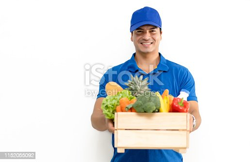 Handsome Caucasian grocery delivery courier man in blue uniform with grocery wooden box with fresh fruit and vegetable. Shopping service concept, isolated standing on white background.