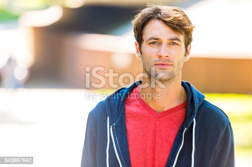Handsome caucasian man with brown hair and scruff wearing a hoodie and a red t-shirt. He is looking at the camera with an instense stare. He has hazel eyes.