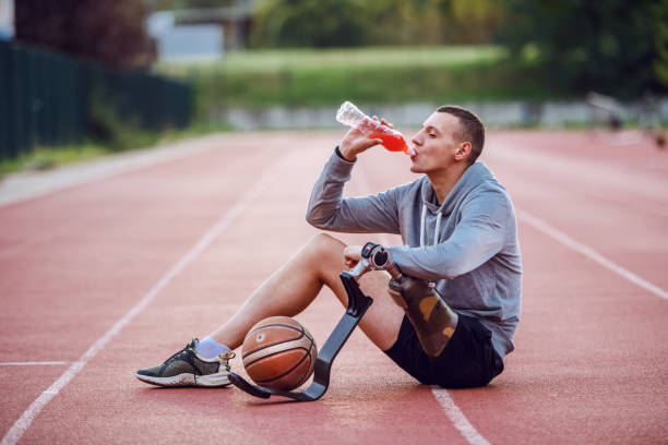 Handsome caucasian sporty handicapped man in sportswear sitting on racetrack and drinking refreshment. Between legs is basketball ball. Handsome caucasian sporty handicapped man in sportswear sitting on racetrack and drinking refreshment. Between legs is basketball ball. persons with disabilities stock pictures, royalty-free photos & images
