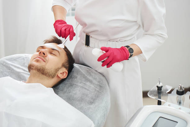 Handsome Caucasian young man at cosmetology procedures in beauty parlor at the beautician. Male dermatologist skin care, closeup face mask