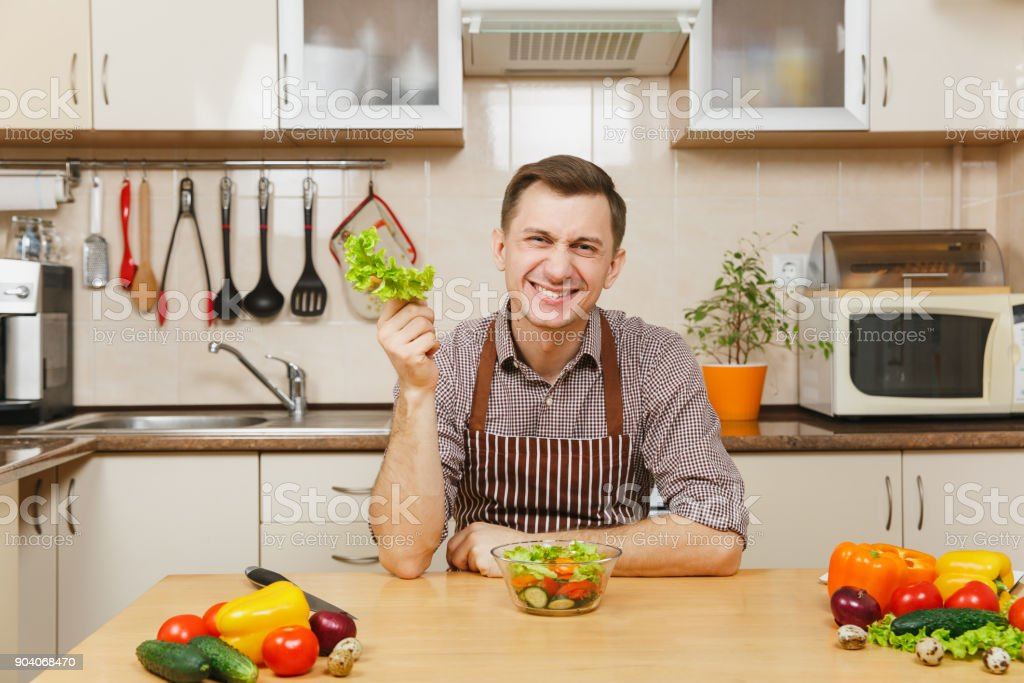 Handsome caucasian young man in an apron, brown shirt sitting at table, cuting and tearing lettuce vegetable for salad with knife in light kitchen. Dieting concept. Cooking at home. Prepare food. stock photo